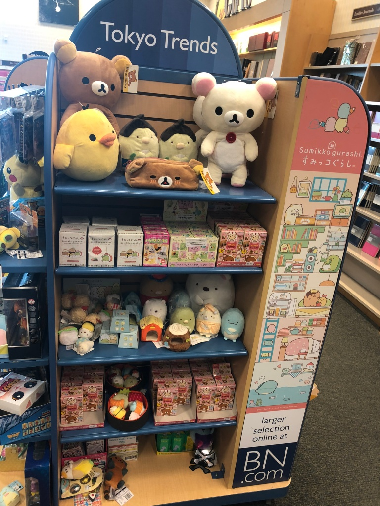 Shelf of Rilakkuma and Sumikkogurashi plush and blindboxes at Barnes and Noble.