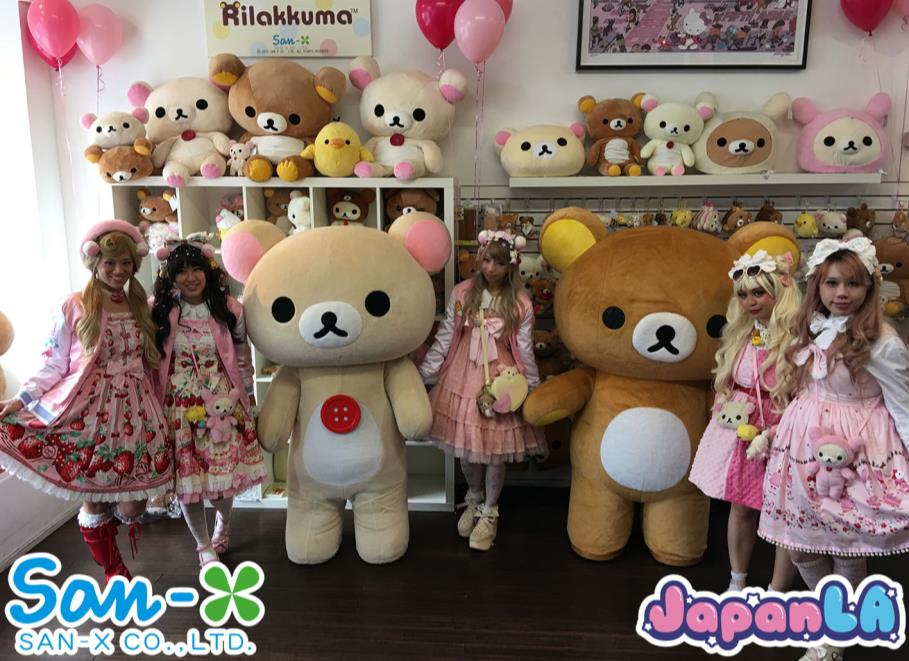 Rilakkuma and Korilakkuma mascots taking a photo with Rilakkuma models in pink dresses for JapanLA. Rilakkuma plush on shelves in the background.