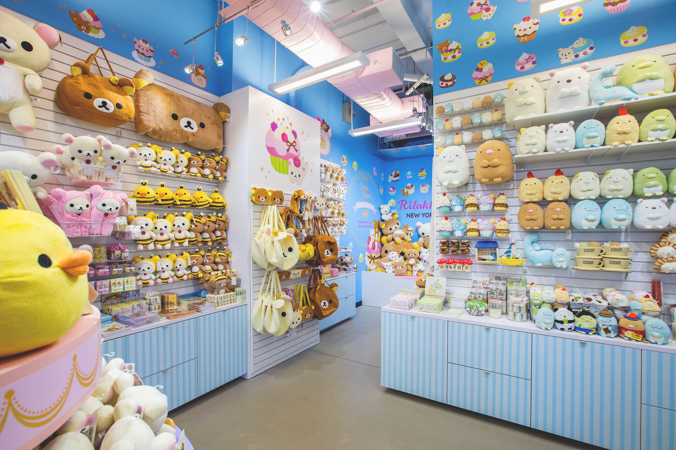 Inside of the Rilakkuma Pop-up shop in New York, showcasing a variety of Rilakkuma and Sumikkogurashi plush as well as the Rilakkuma plush pit. The walls are sky blue with a Rilakkuma sweets pattern of many different Rilakkuma cupcakes and desserts.