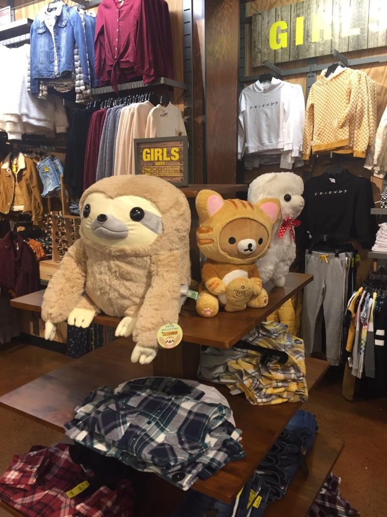 Amuse sloth, alpaca, and Rilakkuma dress as a cat with fish on display at Tilly's.