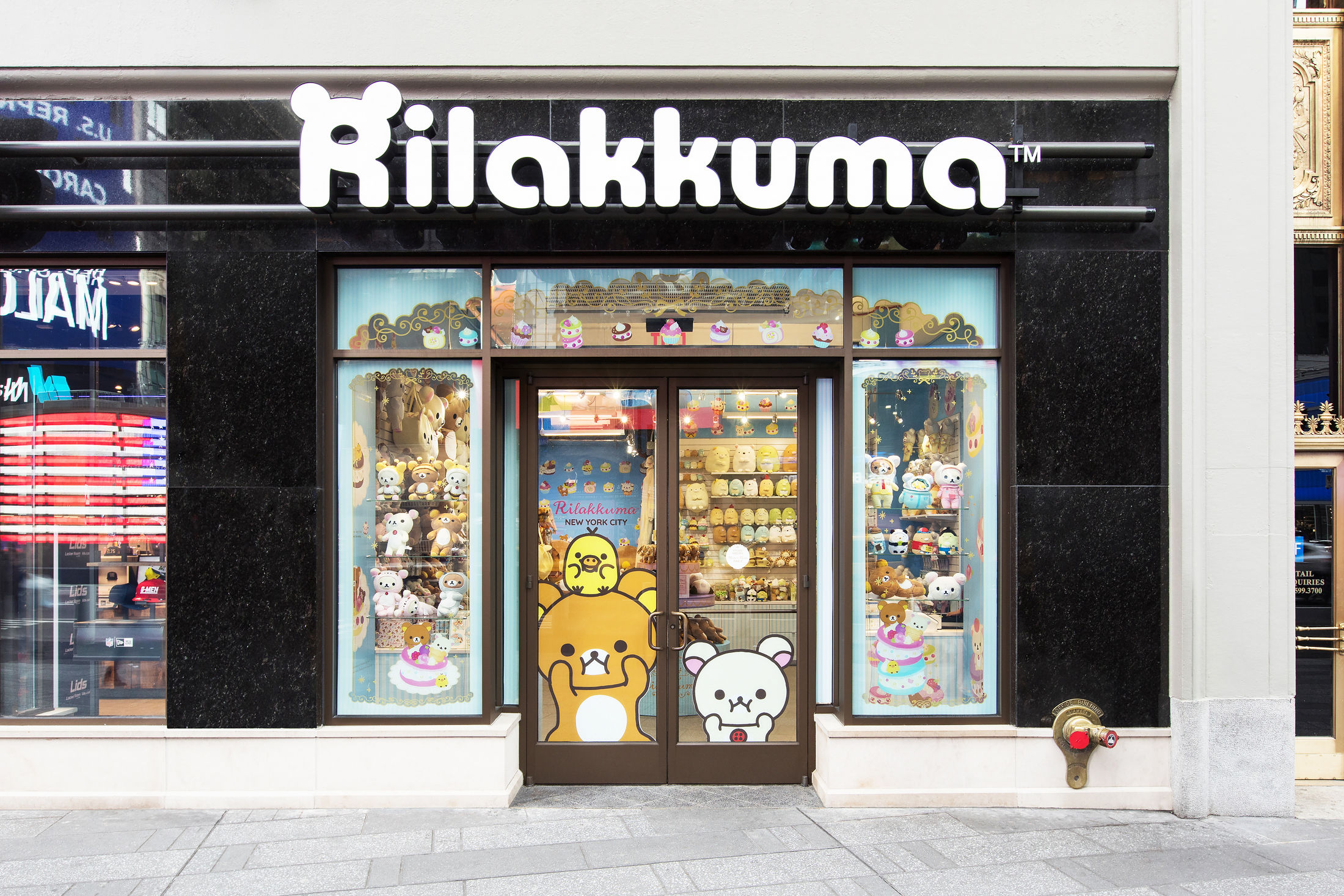 Direct front view of the Rilakkuma pop-up shop in New York with a large Rilakkuma, Korilakkuma, and Kiiroitori decal on the front glass doors and other Rilakkuma sweets decals.